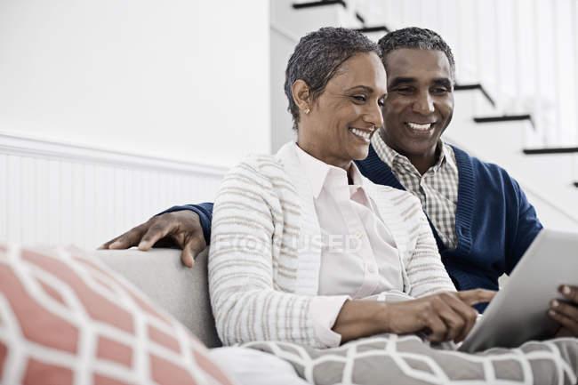 Paar teilt sich ein digitales Tablet. — Stockfoto