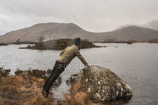 Чоловік, спираючись на скелі — стокове фото