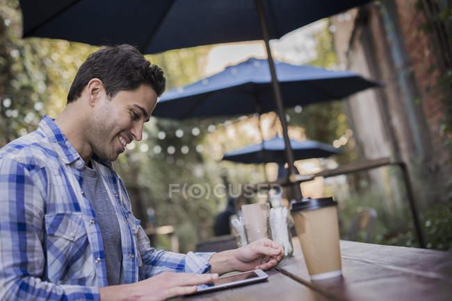 Mann sitzt an einem Cafétisch — Stockfoto