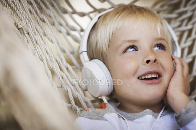 Boy lying in a hammock with music headphones — Stock Photo