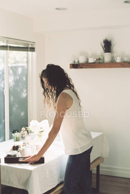 Woman placing a tray with a tea — Stock Photo