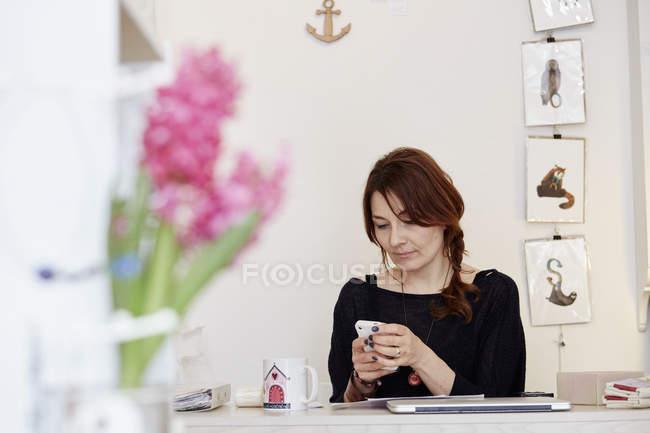 Жінка, сидячи за столом прийняття виклику на смартфоні — стокове фото