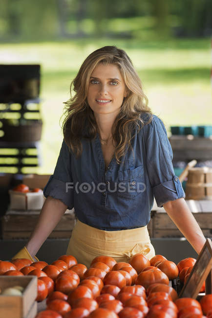 Woman standing at a farm stand stall — Stock Photo