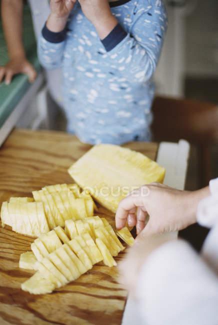 Mulher cortando um abacaxi fresco — Fotografia de Stock