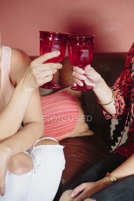 Mulheres segurando taças de vidro vermelho — Fotografia de Stock