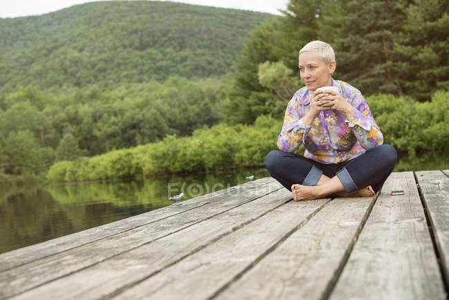 Woman sitting on a dock with cup of coffee — Stock Photo