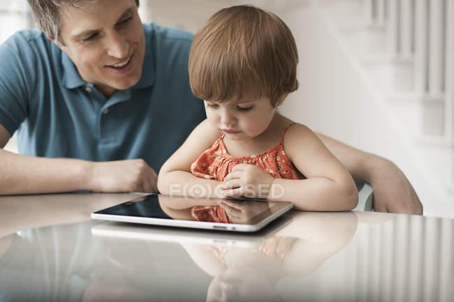 Vater und Tochter Blick auf eine digital-Tablette — Stockfoto