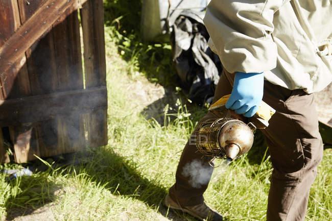Apicoltore in una muta con un fumatore in mano — Foto stock