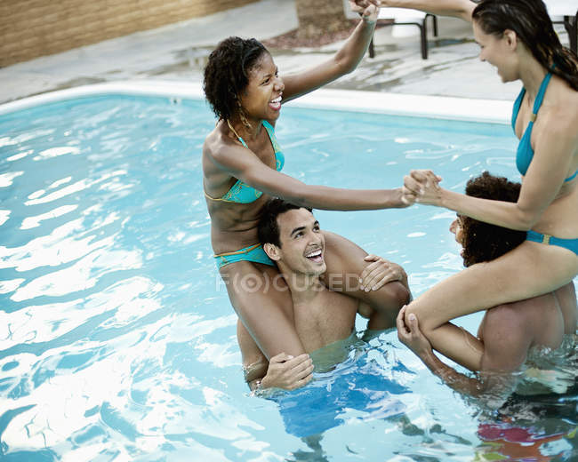 Couples in the swimming pool — Stock Photo