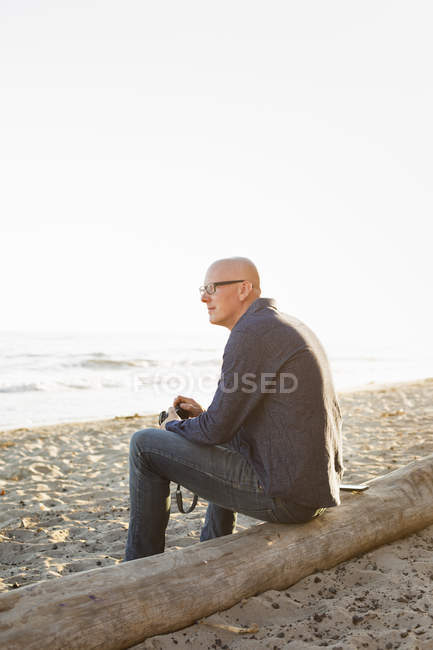 Bald man sitting on a log — Stock Photo