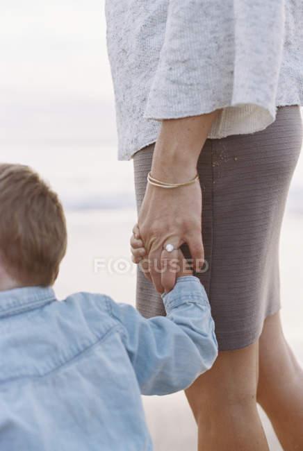 Mujer con hijo de pie en una playa de arena - foto de stock