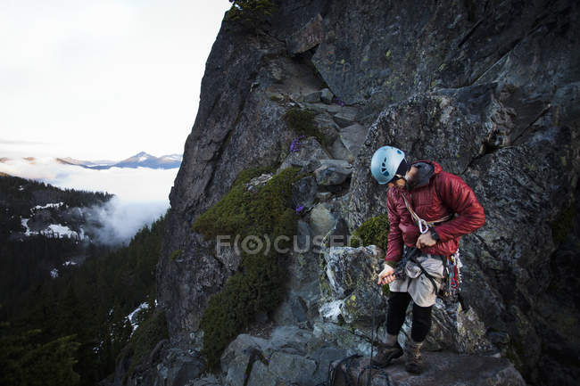 Bergsteiger steht auf dem Gipfel — Stockfoto