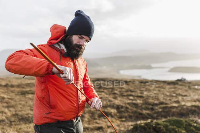 Uomo che tiene un picchetto della tenda — Foto stock