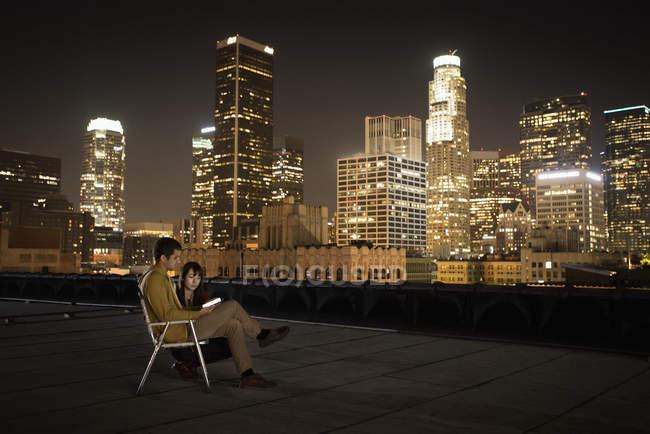 Casal em um telhado com vista para a cidade à noite — Fotografia de Stock