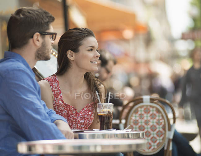 Couple assis dans des sièges dans un café trottoir — Photo de stock
