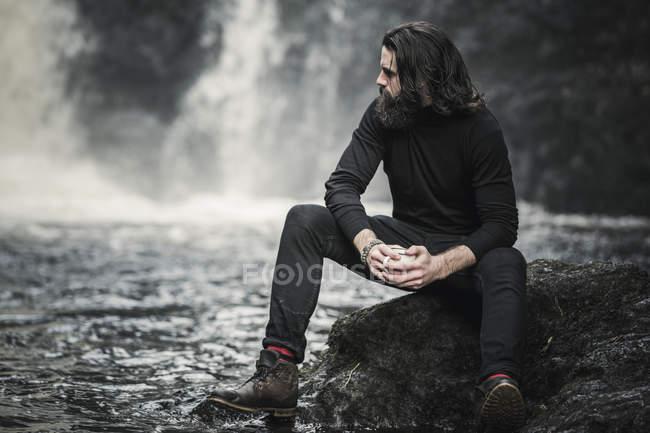 Uomo seduto da un ruscello che scorre veloce — Foto stock