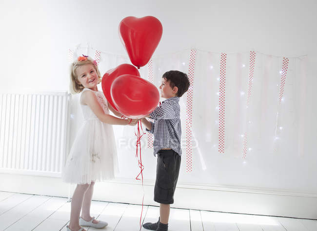 Young boy and girl holding balloons. — Stock Photo