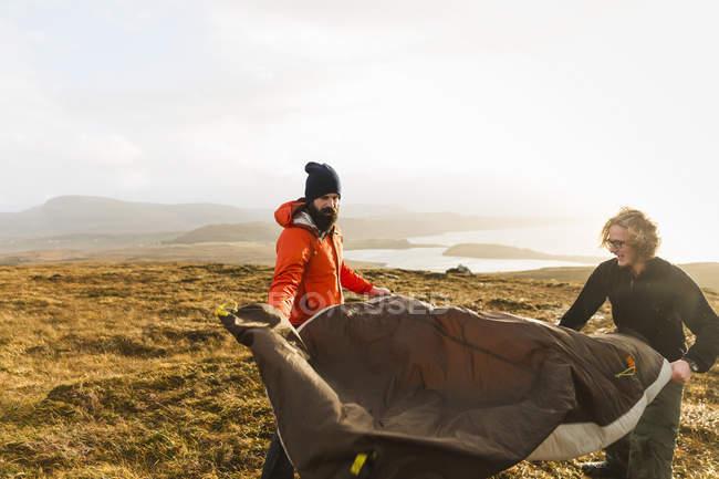 Männer, die ein kleines Zelt halten und aufstellen — Stockfoto