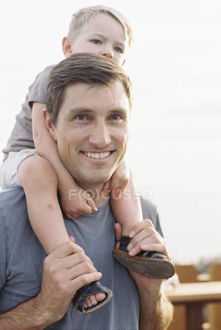 Человек, несущий сына на своих плечах . — стоковое фото