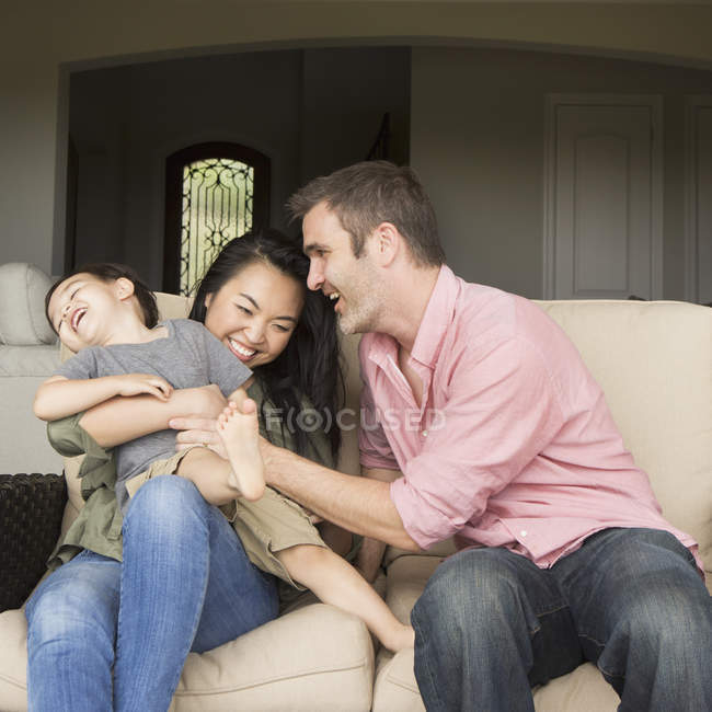 Man and woman playing with young son. — Stock Photo