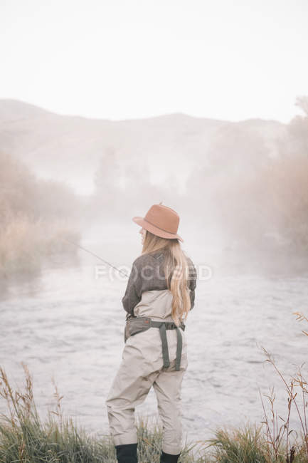 Fisherwoman standing on the banks of a river — Stock Photo