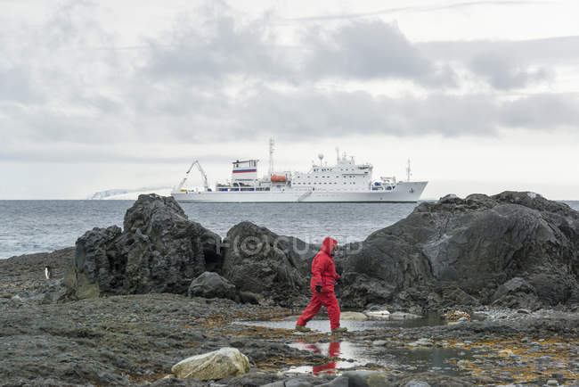 Homme marchant le long des rochers au bord de la mer — Photo de stock