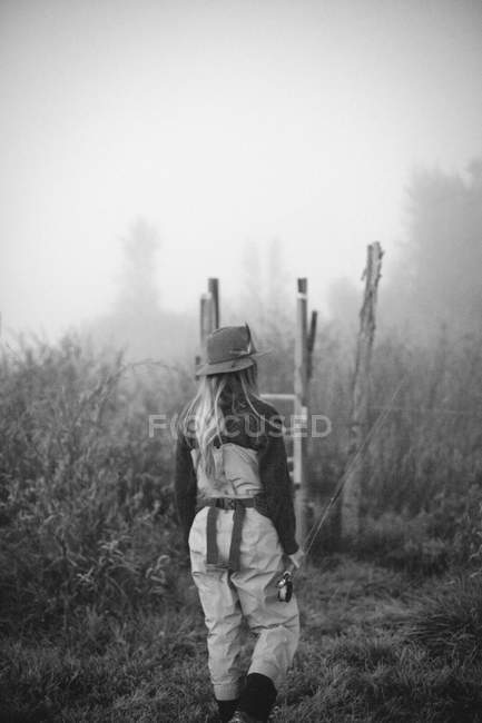 A woman carrying a fishing rod — Stock Photo
