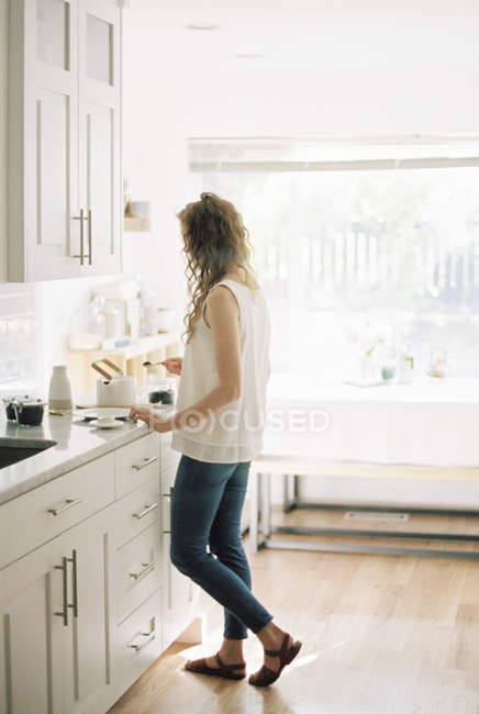 Woman standing in a kitchen — Stock Photo