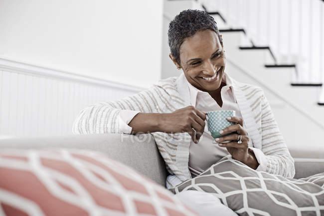 Женщина сидит на диване — стоковое фото
