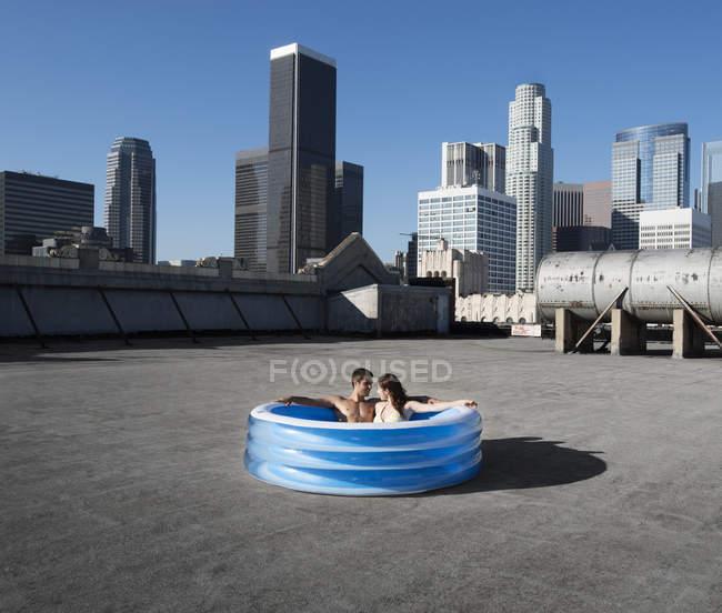 Пара в надувном бассейне на крыше — стоковое фото