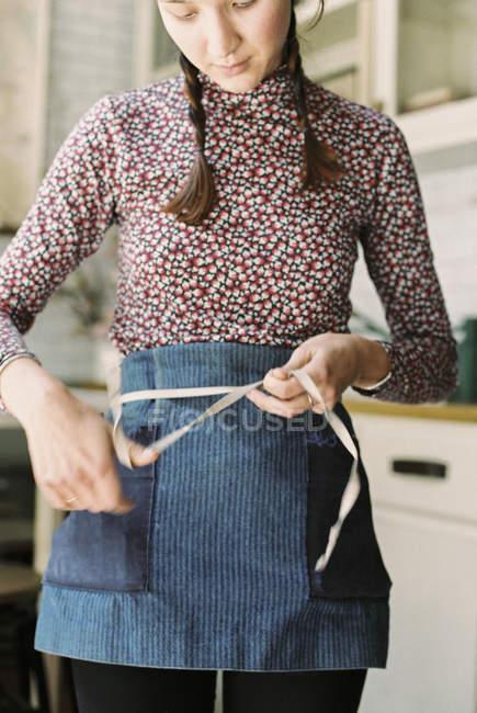 Женщина, связывая ленты фартук — стоковое фото