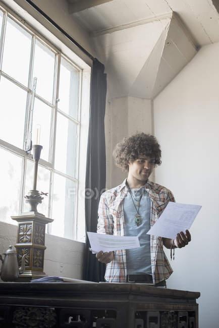 Человек за столом, держа документы — стоковое фото