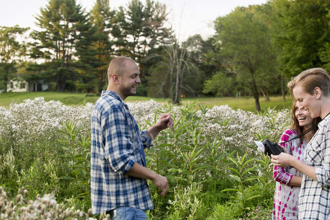 Man and two women standing in a wildflower meadow — Stock Photo