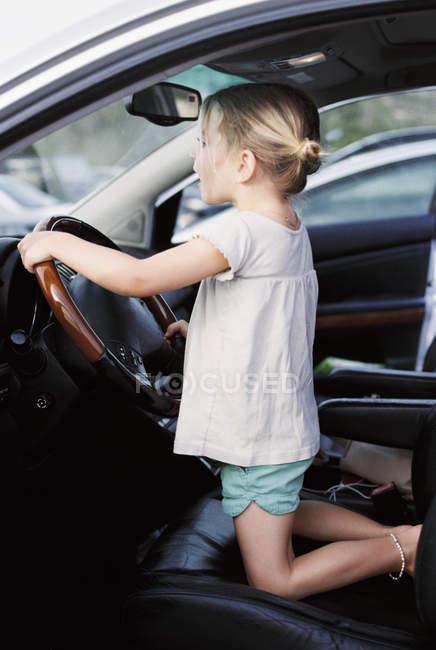 Jeune fille à genoux sur le siège du conducteur d'une voiture — Photo de stock