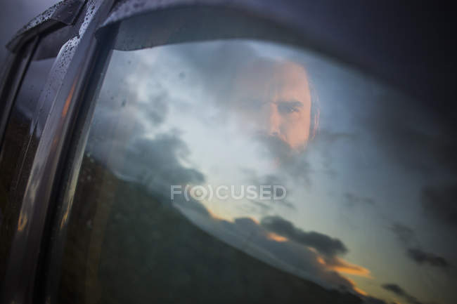 Man sitting in a car looking out. — Stock Photo