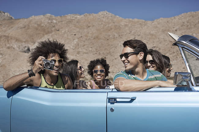 Friends in a pale blue convertible — Stock Photo