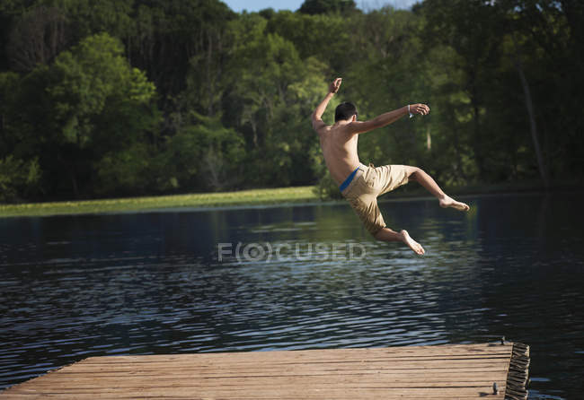 Menino pulando em uma piscina calma — Fotografia de Stock