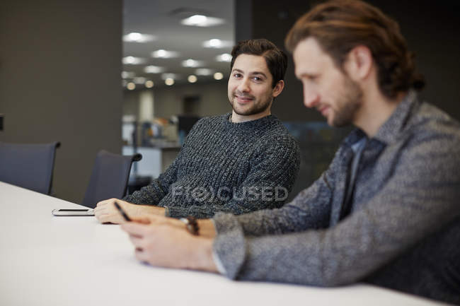 Two men seated at a table — Stock Photo