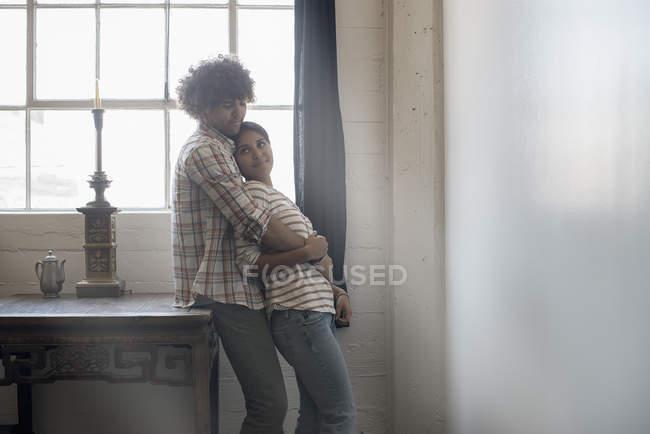 Coppie che stanno fianco a fianco da una finestra — Foto stock