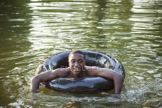 Homem flutuante com flutuador de natação pneumático — Fotografia de Stock