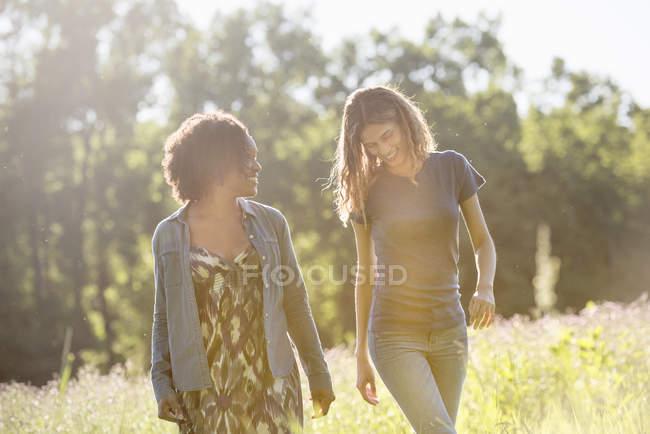 Two women walking through a field — Stock Photo