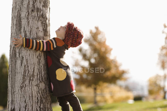 Girl with her arms around a tree — Stock Photo