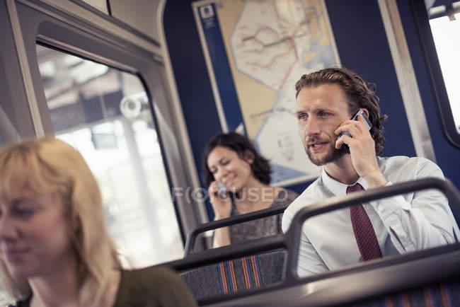 Pessoas no ônibus, dois falando em telefones celulares — Fotografia de Stock