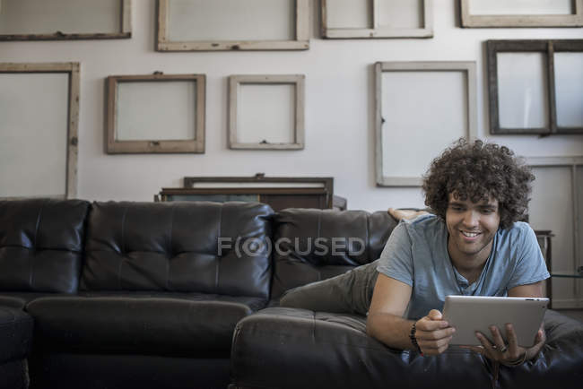 Man in sofa using a digital tablet. — Stock Photo