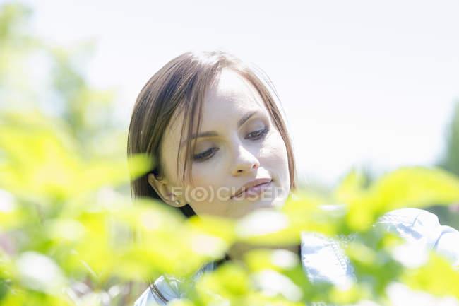 Donna all'aperto circondata da piante verdi — Foto stock