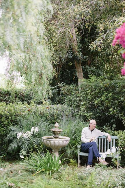 Людина сидить на лавці дерев'яні — стокове фото