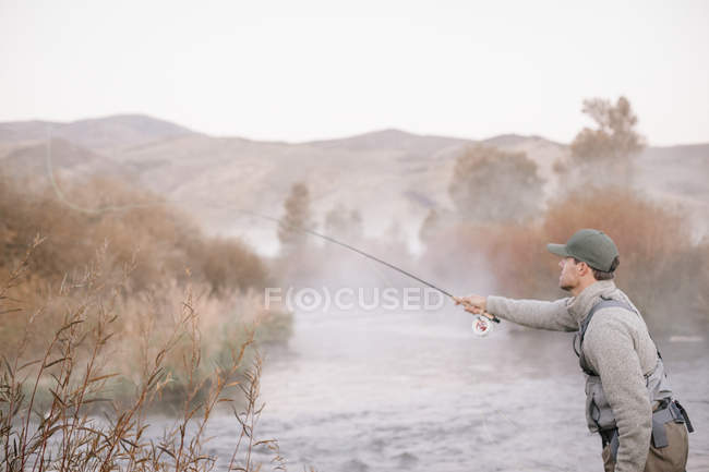 Man flyfishing from a riverbank. — Stock Photo