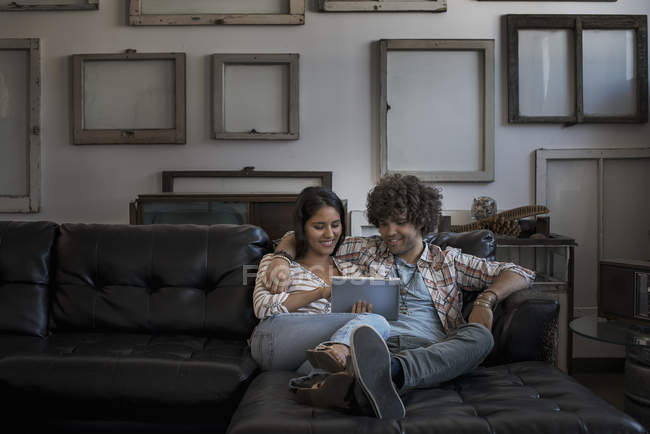 Couple on a sofa, looking at a digital tablet. — Stock Photo