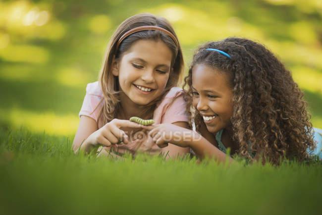 Girls holding a green caterpillar — Stock Photo