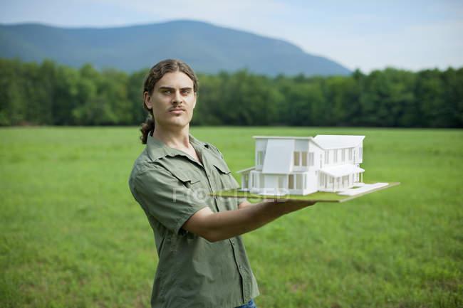 Особа, що займає масштабна модель будинку — стокове фото